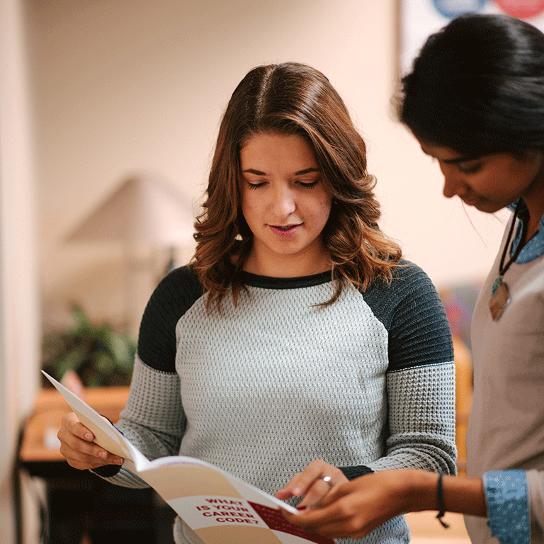 Two girls looking up a career code in a booklet.